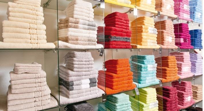Viele verschiedene bunte Handtücher in gläsernem Regal