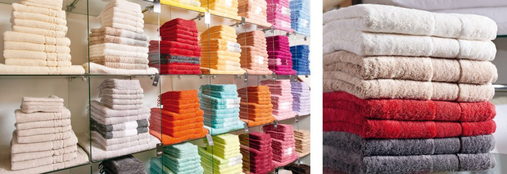Viele bunte Handtücher im Regal