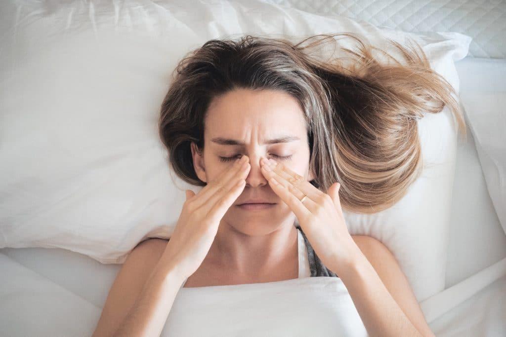 Frau liegt im Bett und wird von Allergie geplagt