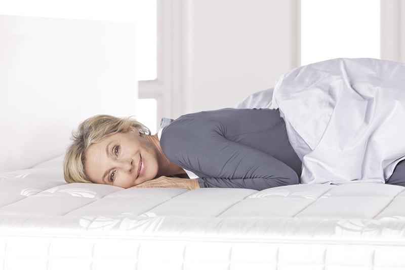 Lächelnde Frau liegt auf gemütlicher Matratze